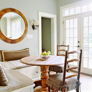 small corner banquette with round table and round mirror