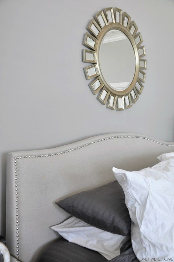 neutral master bedroom, gray and white bedding, white headboard, sunshine mirror w/gold