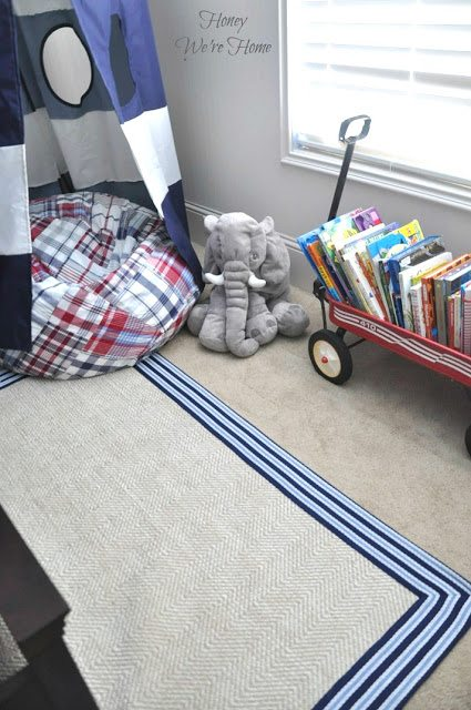 Big boy room with Pottery Barn striped canopy, chenille border rug and wagon to store books