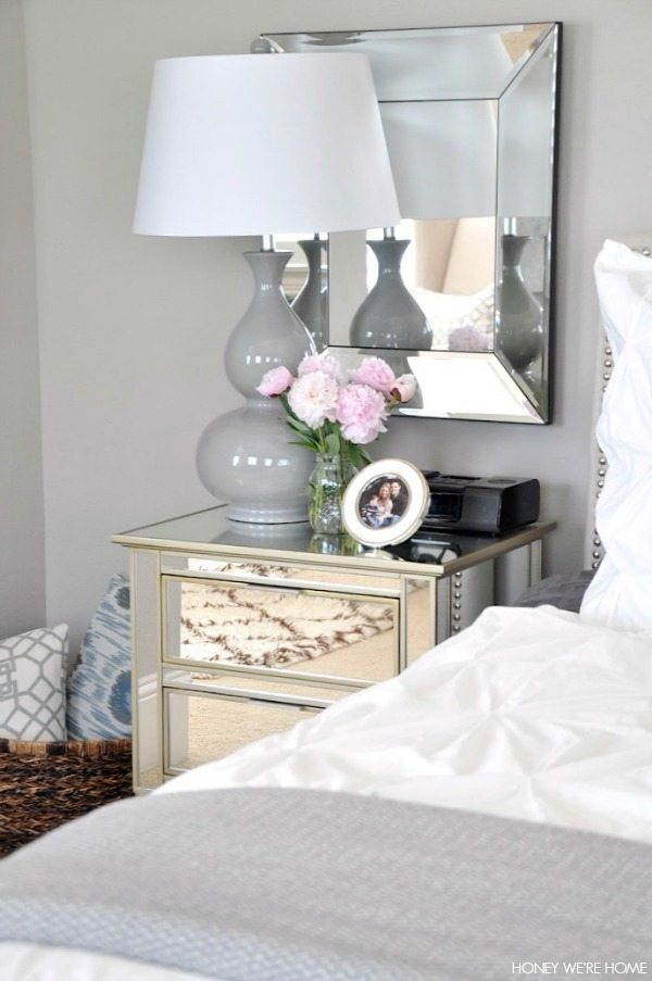 neutral master bedroom, white and gray bedding mirrors, lamp, night stand and pillows