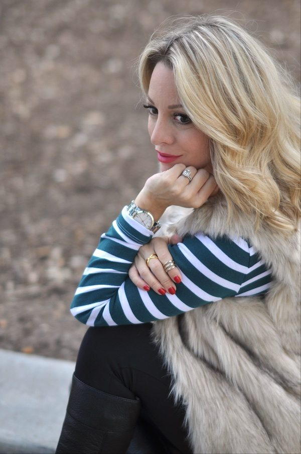Gorjana ring, faux fur vest, striped top, black maternity leggings, black boots, necklace and watch.