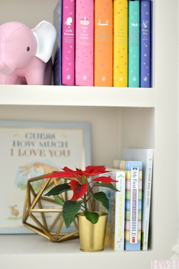 Festive holiday nursery bookshelf with pink and gold decorations.   Honey We're Home