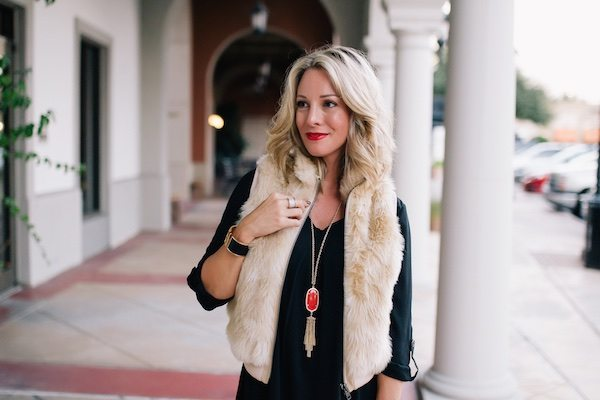 Fall fashion - little black dress with red Kendra Scott necklace and fringe heels + faux fur vest