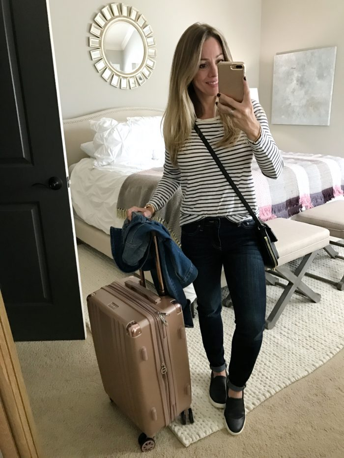 Fall fashion comfy travel outfit - striped top, jeans and slip on sneakers with rose gold luggage