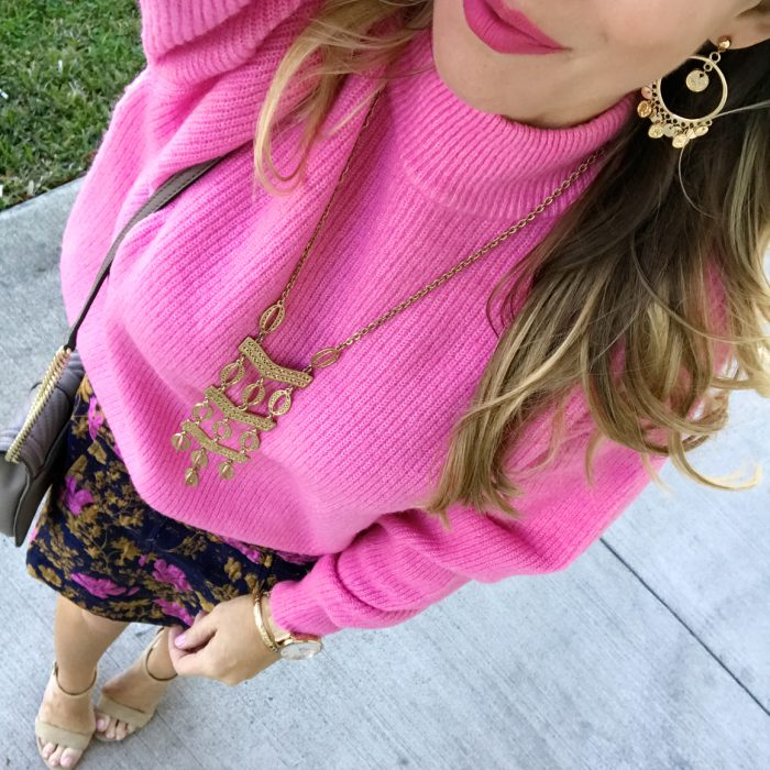 pink sweater with brocade skirt and gold accessories