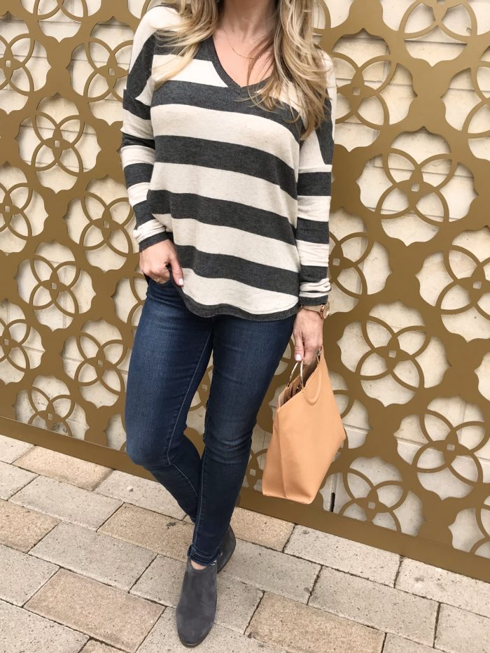 striped pullover and tan bag