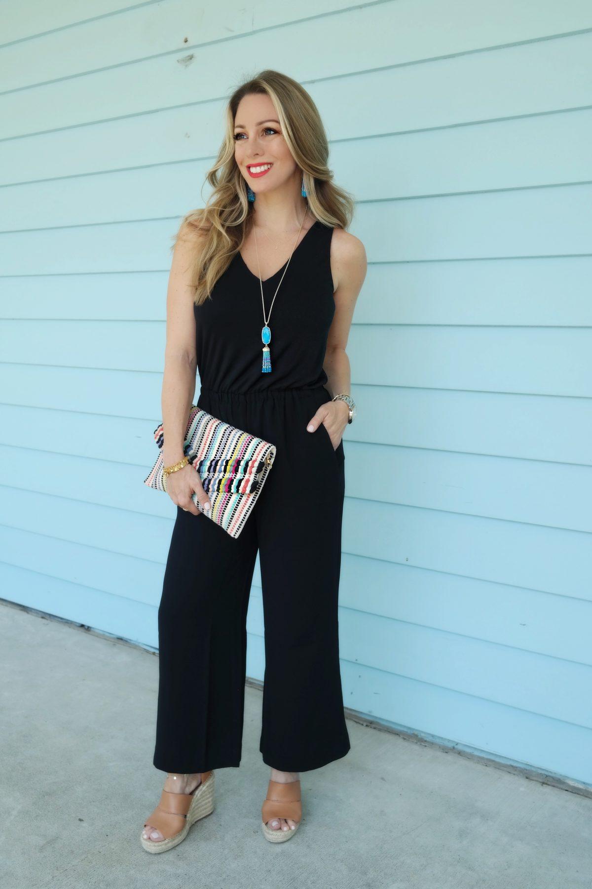 Black Loft jumpsuit with striped clutch and Kendra Scott jewelry
