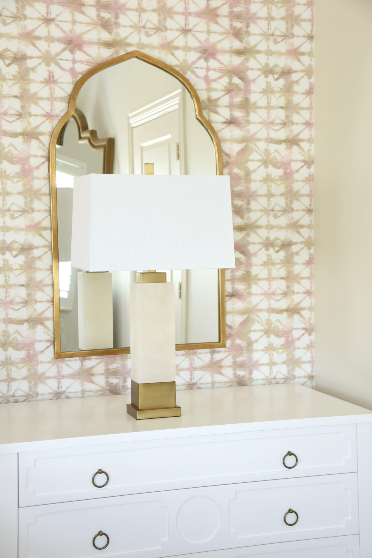 Master Bedroom with gold arched mirror and marble lamp