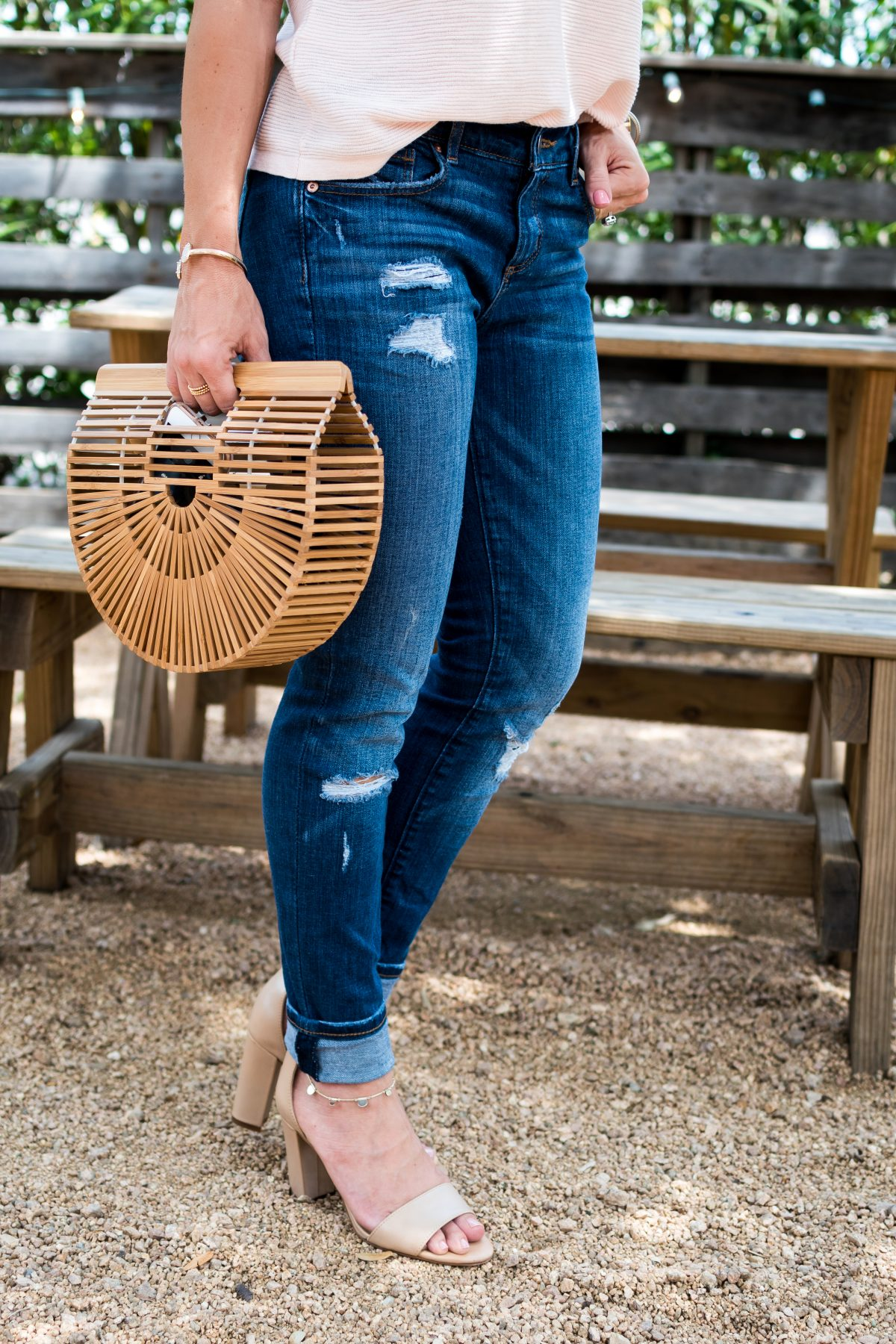 Spring Outfit- pink flutter sleeve top with distressed jeans, wooden bag, and heels