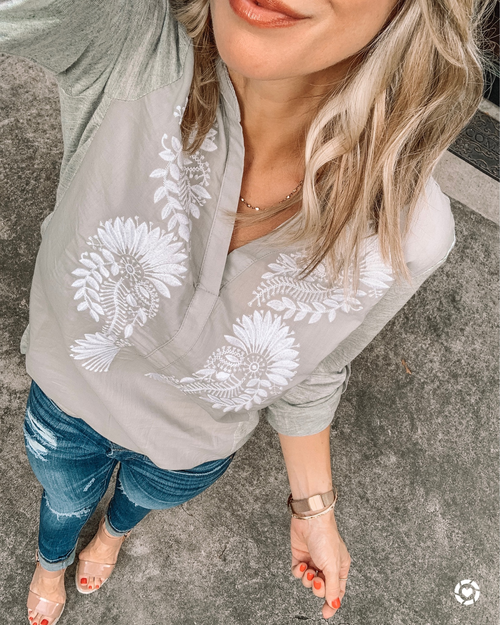 grey and white embroidered top with jeans