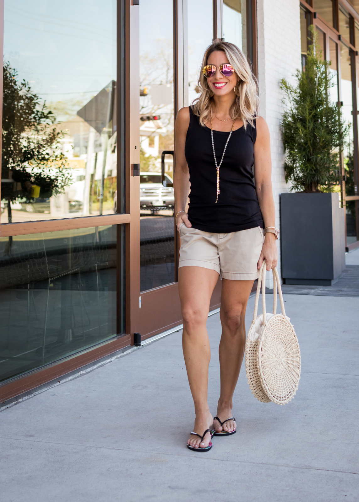 Khaki shorts black tank top and flip flops