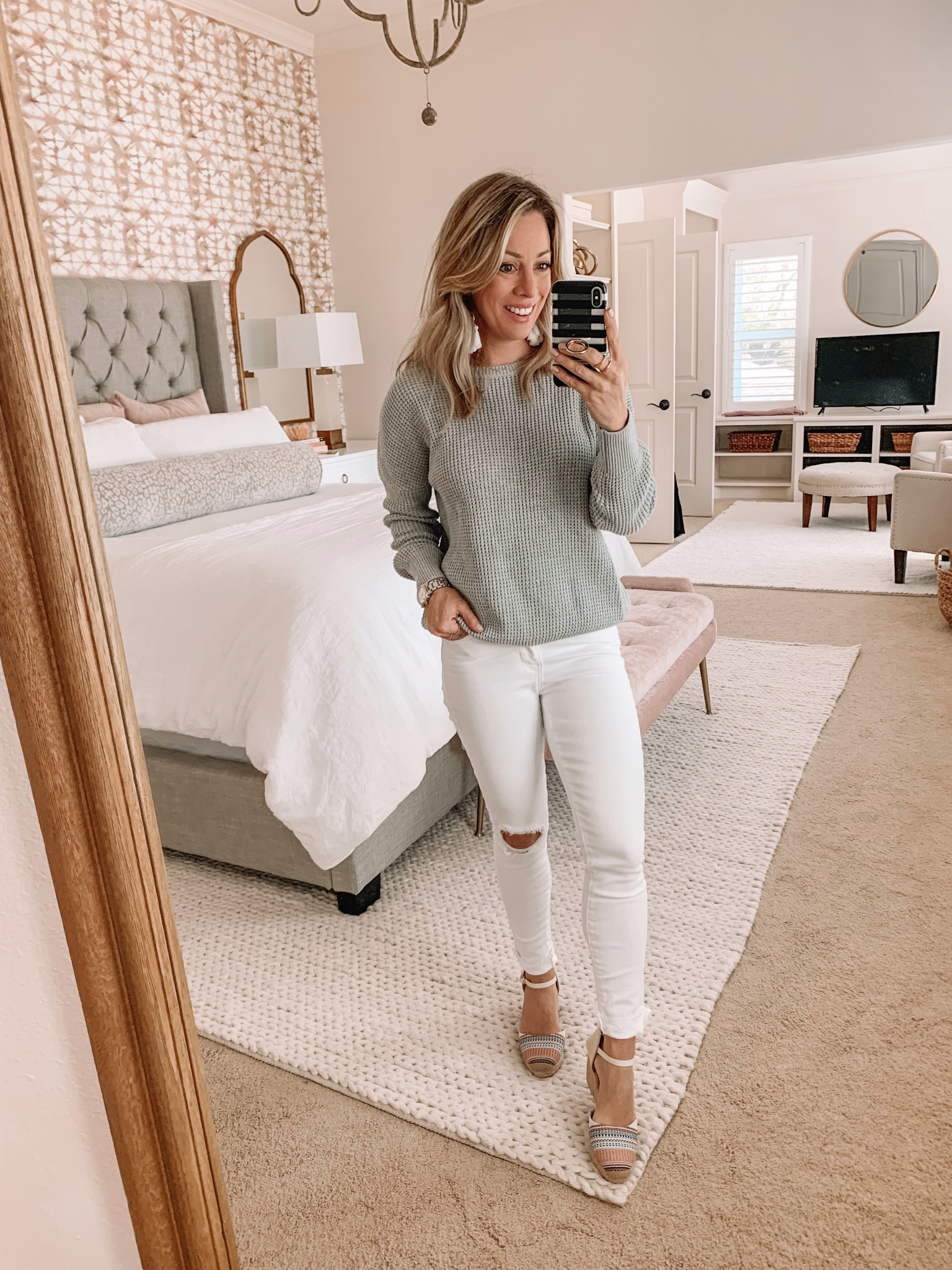 Grey crossback sweater and white jeans