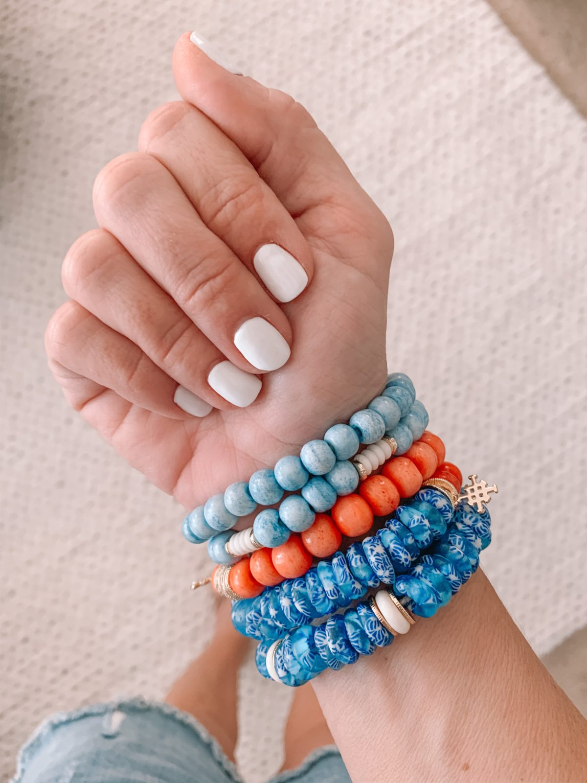 beaded bracelets and white nail polish